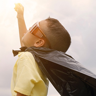 child with cape facing sky with fist up