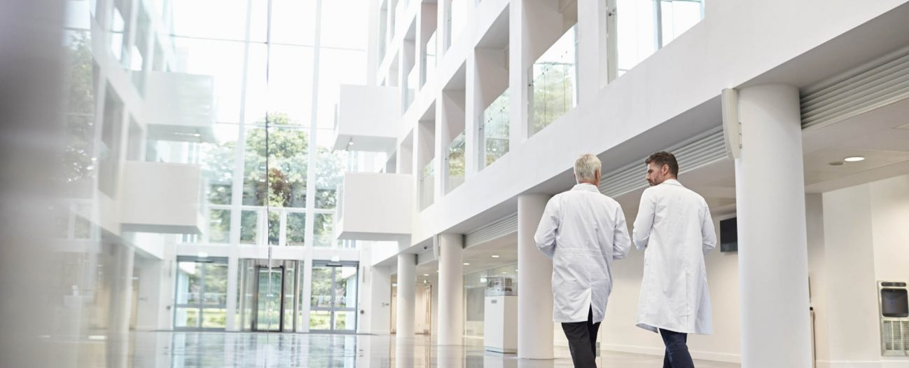 Aciron two doctors walking down a hospital hallway